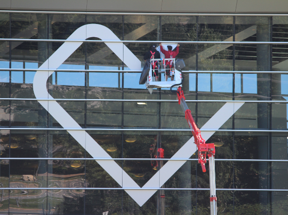 Worker placing new logo on building