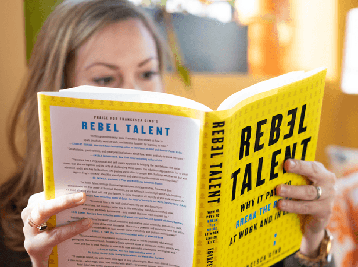 "Caucasian woman reading the book ""Rebel Talent"" by Francesa Gino"