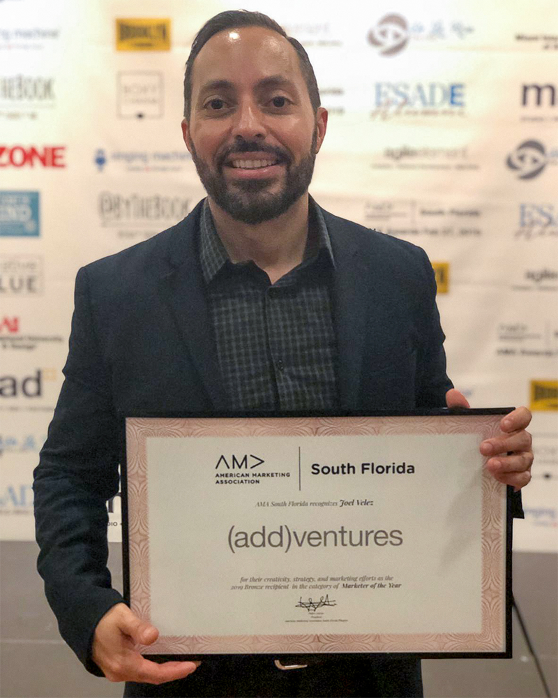 Joel from (add)ventures team with award