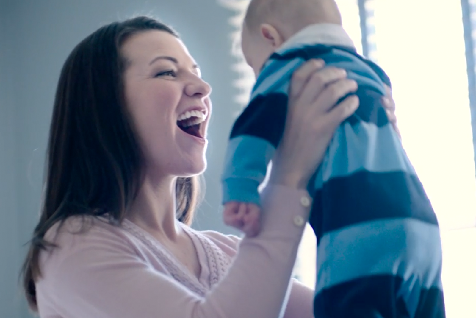 Woman holding up and smiling at her baby