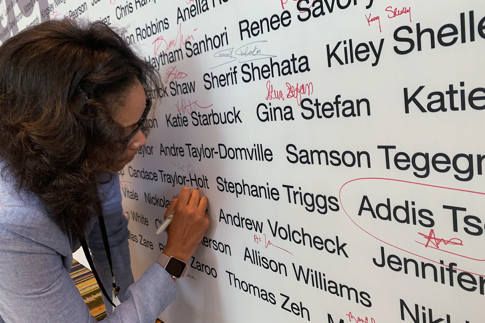 Woman writing her signature on a wall of CVS Paragon Award recipients.