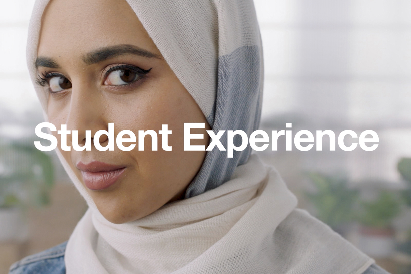student in head scarf with word student experience across screen